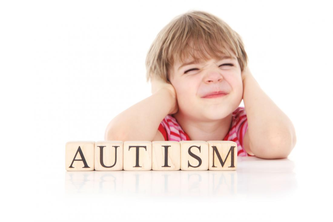 child-covering-its-ears-witch-cubes-spelling-out-autism